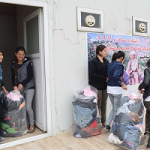 Many Christians receiving bags of donated clothes in Iraq refugee camp.
